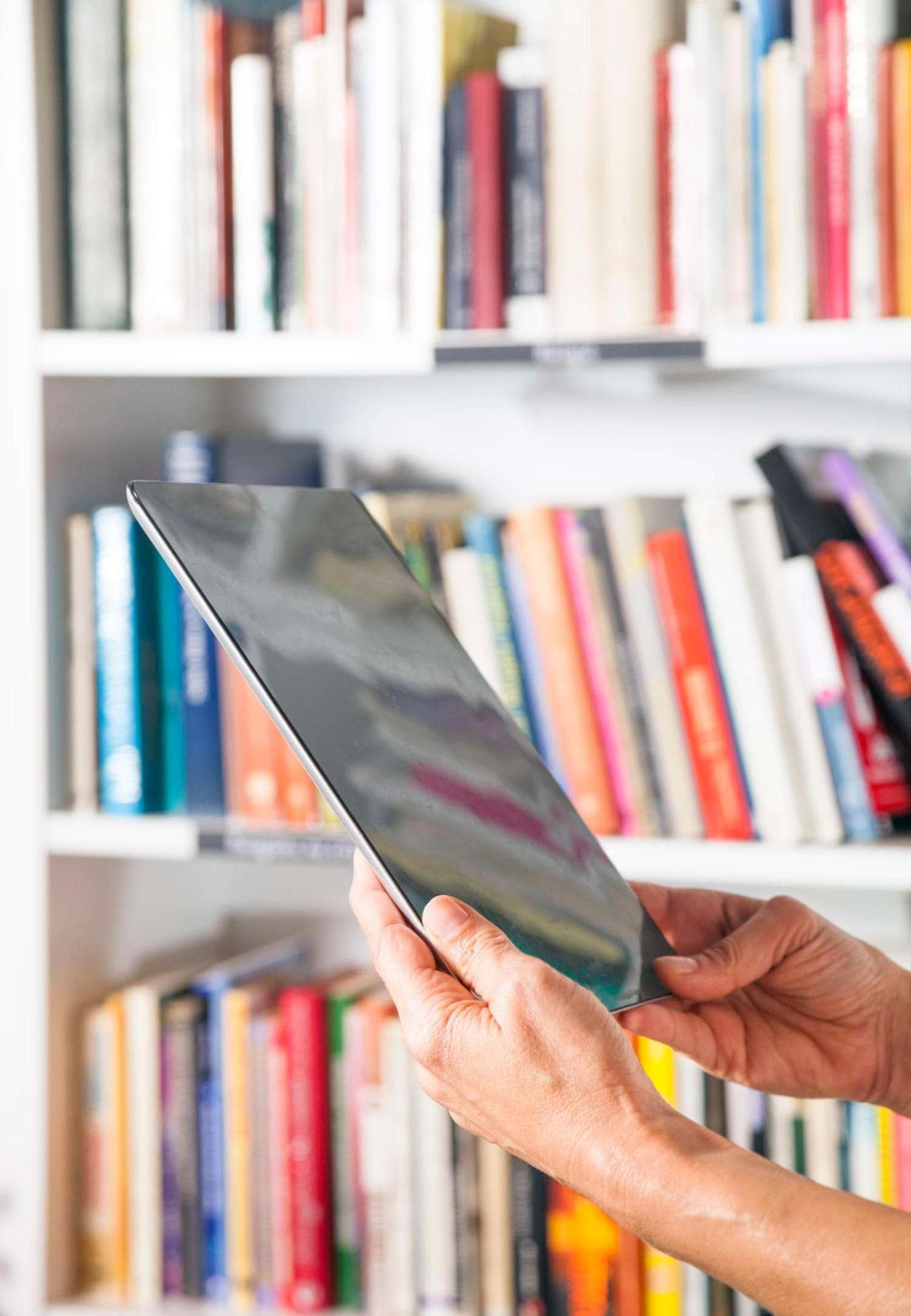 Person using a tablet with a  shelf of books in background